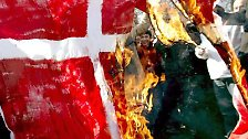 """In der muslimischen Welt brennt Dänemarks Flagge. Die dänische Zeitung """"Jyllands-Posten"""" hatte als erste Mohammed-Karikaturen veröffentlicht. Eine von ihnen zeigt den Propheten Mohammed mit einem Turban in Form einer Bombe."""