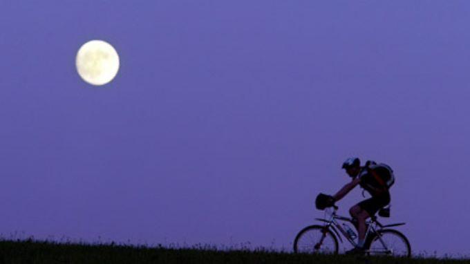 """""""Der ist doch riesig!"""" Radfahrer mit Mond, aufgenommen mit einem starken Teleobjektiv."""