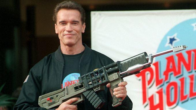 """Arnold Schwarzenegger posiert mit der """"Railgun"""" aus dem Actionfilm """"Eraser""""."""
