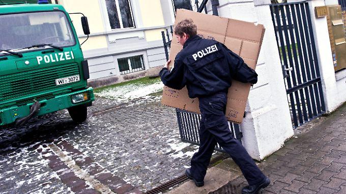 Kartonweise Beweismittel: Ein Polizei holt vor einer Frankfurter Villa Nachschub für die Kollegen.