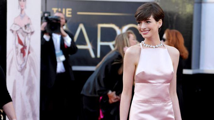 Hathaway setzte beim Gang über den roten Teppich auf ein Kleid von Prada.