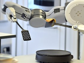 Hier dreht der Roboter in der Laborküche einen Pfannkuchen um.