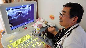 In der Präfektur Fukushima: Mit einem Ultraschall untersucht ein Arzt die Schilddrüse einer jungen Frau.