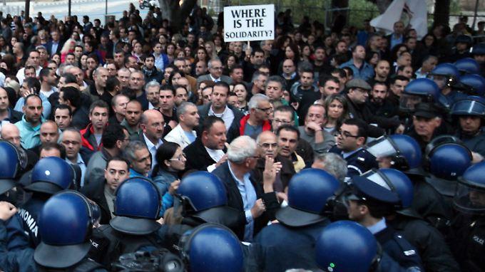 Vor dem Parlament demonstrieren viele Menschen gegen den Plan, die Laiki Bank abzuwickeln.