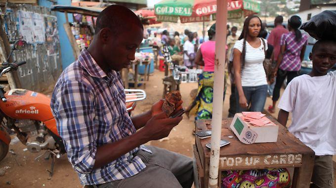 Junger Africell-Mitarbeiter an seinem Stand in Freetown, Sierra Leone. Die Mobiltelefonie ist in Afrika im letzten Jahrzehnt geradezu explodiert. Denn ohne flächendeckendes Festnetz ist sie die einzige Möglichkeit der Telekommunikation.