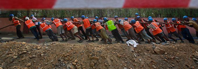 Mumbai im Mai 2013: Arbeitskräfte sind billiger als Maschinen, schwere Kabelstränge werden in Wirtschaftsmetropole noch mit Muskelkraft verlegt.
