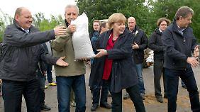 Foto mit Sandsack: Angela Merkel in Pirna.