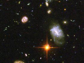 Ein tiefer Blick ins All zeigt eine chaotische Ansammlung von Galaxien in bizarren Formen. Weiter als 13,7 Milliarden Lichtjahre können wir nicht schauen.