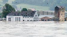 Wie entfesselt strömt das Wasser der Donau in die Stadt nahe der Isarmündung.