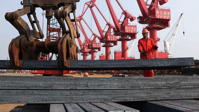 Arbeiter löschen eine Ladung Stahlbarren in einem Hafen in Lianyungang.