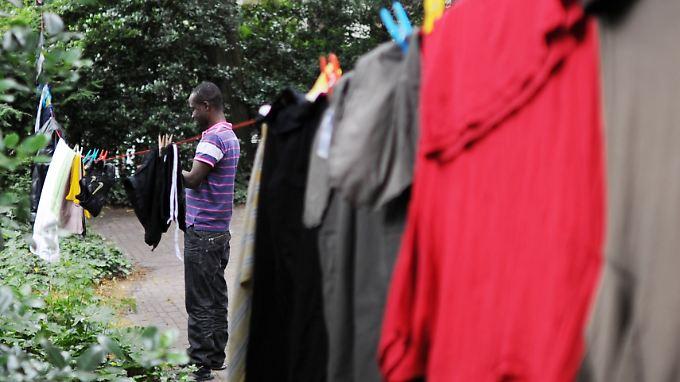 Ein afrikanischer Flüchtling hängt im Garten der Hamburger St.-Pauli-Kirche seine Wäsche auf.
