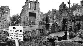 """Eine Gedenktafel, deren Text lautet: """"Gedenkstätte: Eine Gruppe von Männern wurde hier von den Deutschen massakriert und verbrannt. Besinnt euch!"""""""