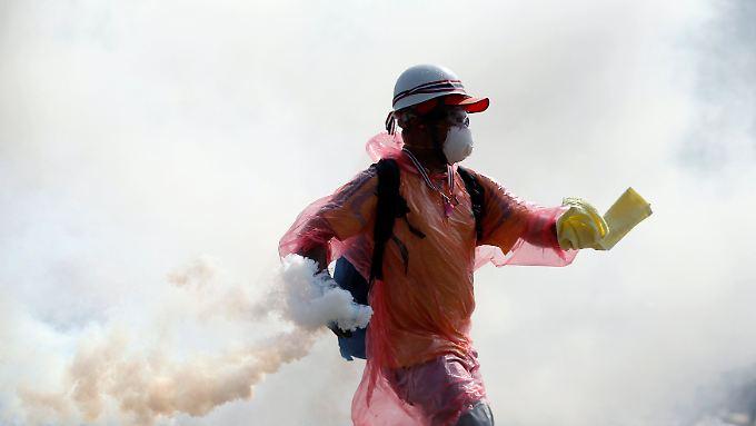 Vor dem Regierungssitz in Bangkok wirft ein Demonstrant Tränengas-Kartuschen auf die Polizei.