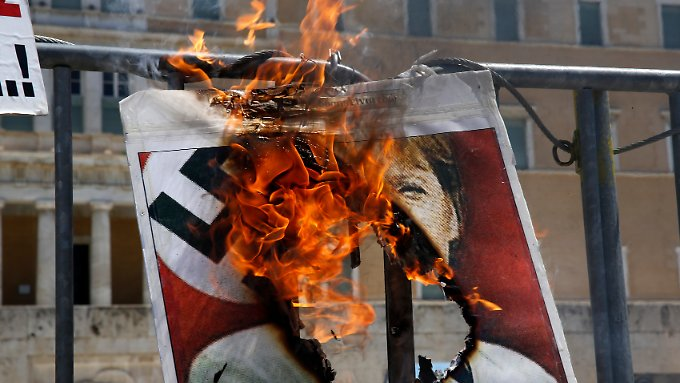 Vor dem griechischen Parlament in Athen brennt ein Poster, das Bundeskanzlerin Angela Merkel verunglimpft.