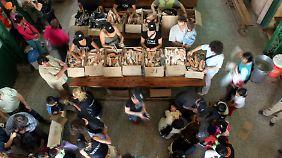"""In einer Suppenküche in Buenos Aires werden """"Tom's""""-Shuhe an Arme verteilt."""