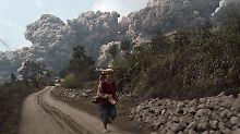 Eine Anwohnerin flieht vor der gewaltigen Aschewolke.