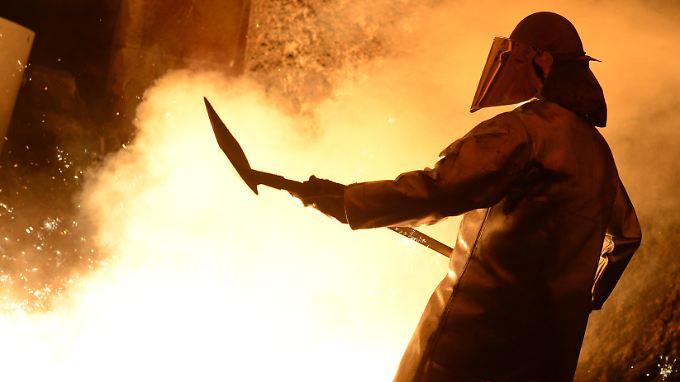 Ein Salzgitter-Stahlwerker schaufelt nach dem Anstich eines Hochofens Sand in den Fluss des glühenden Stahls.