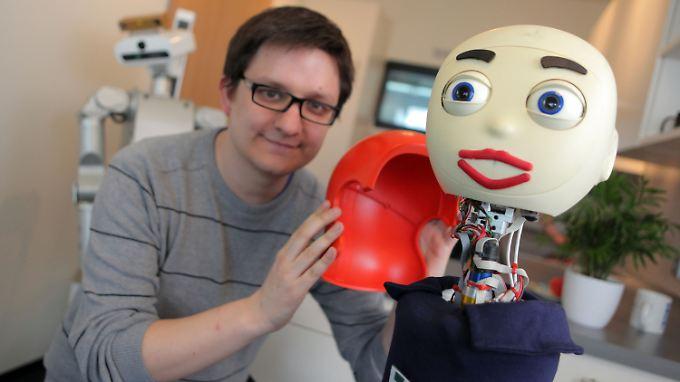 """Andreas Kipp von der Uni Bielefeld verpasst Roboter """"Flobi"""" eine rote Haartracht."""