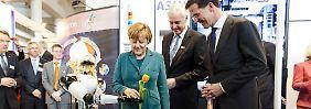 """Stereotype Symbolpolitik: Unter den Augen des niederländischen Premiers Mark Rutte (r.) überreicht Roboter """"Frau Antje"""" (l.) der Kanzlerin zur Messeröffnung eine Tulpe. Die Industriemesse dauert noch bis 11. April. Partnerland sind in diesem Jahr die Niederlande."""