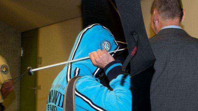 Der Zeuge versteckt sein Gesicht hinter einem Regenschirm. An seiner Seite ist sein Rechtsbeistand.