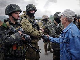Anwohner versuchen mit den ukrainischen Soldaten zu sprechen und sie abzuhalten.