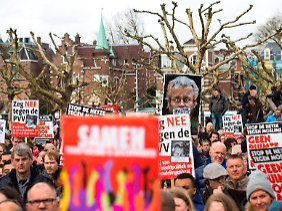 """Nach Wilders' Auftritt in Den Haag gab es Proteste gegen ihn. Er hatte dem Publikum zugerufen: """"Wollt Ihr weniger oder mehr Marokkaner in eurer Stadt und in den Niederlanden?"""" Als Antwort skandierte die Menge """"Weniger! Weniger!"""" Wilders versprach darauf: """"Wir werden uns darum kümmern."""""""