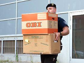 Ein Polizeibeamter trägt Kartons mit Akten zu einem Transporter.