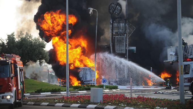Die israelische Feuerwehr versucht eine brennende Tankstelle zu löschen, die nach einem Raketenangriff der Hamas in Flammen aufgegangen war.