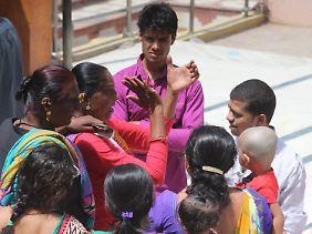 Die Transsexuelle Sudha (M.) klatscht im Hindu-Tempel in Becharaji in ihre Hände. Kanta (l.) hält das eingesammelte Geld in der Hand.