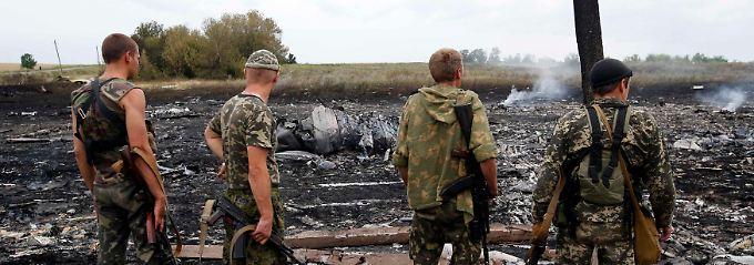 Pro-russische Separatisten begutachten die Wrackteile der Boeing 777: Die Trümmerteile liegen in weitem Umkreis verstreut, es gibt keine Aussicht auf Überlebende.