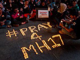 Angehörige der Opfer zünden Kerzen für die Toten an.