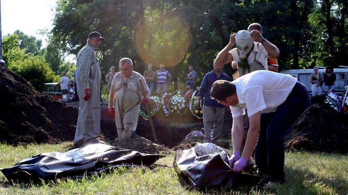 Leichen werden aus dem Grab geborgen.