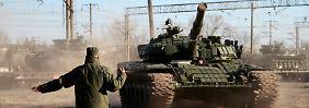 Ein Soldat weist einen russischen T-72-Panzer nach dem Transport per Zug den Weg zu seinem neuen Bestimmungsort.