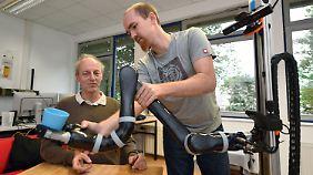 Benjamin Stähle (r), Mitarbeiter an der Hochschule Ravensburg-Weingarten, bereitet einen Serviceroboter vor. Wolfgang Ertel, Professor für Informatik, sitzt am Tisch und lässt sich bedienen.