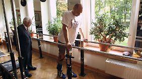 Darek Fidyka kann mit einer Gehhilfe wieder laufen (links Professor Wagih el-Masri).