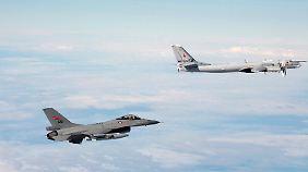 Politisch brisante Begegnung im europäischen Luftraum: Ein norwegischer Abfangjäger vom Typ F-16 (l.) kontrolliert einen russischen Tu-95-Bomber über dem Nordmeer.