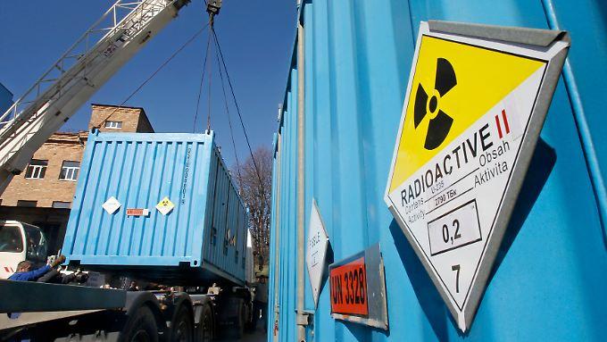 Arbeiter verladen einen Container mit hoch angereichertem Uran in Kiew.