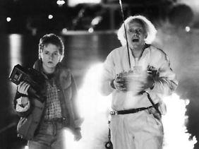 """Marty McFly (l.) und der Erfinder Dr. E. Brown staunen in """"Zurück in die Zukunft"""" über ihre Zeitmaschine. Außerhalb des Films ist ein Zeitsprung kürzer - und funktioniert etwas anders."""