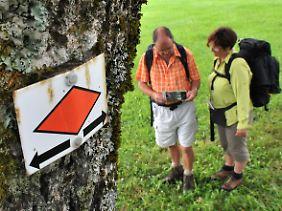 Beliebtes Hobby: Wanderer bei St. Märgen im Schwarzwald, im Vordergrund die rote Raute, Symbol für den Westweg durch den Schwarzwald.