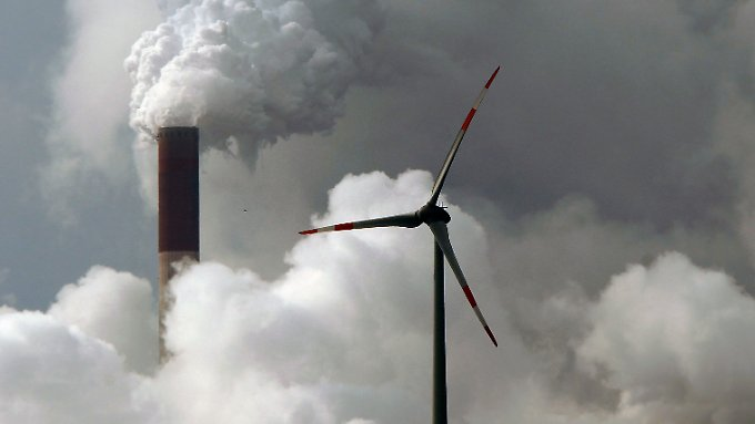 Eine Windturbine dreht sich vor den Schloten des Gelsenkirchener Kohlekraftwerks Scholven.