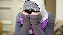 Die Angeklagte verbirgt ihr Gesicht zu Beginn des Prozesses vor den Fotografen.