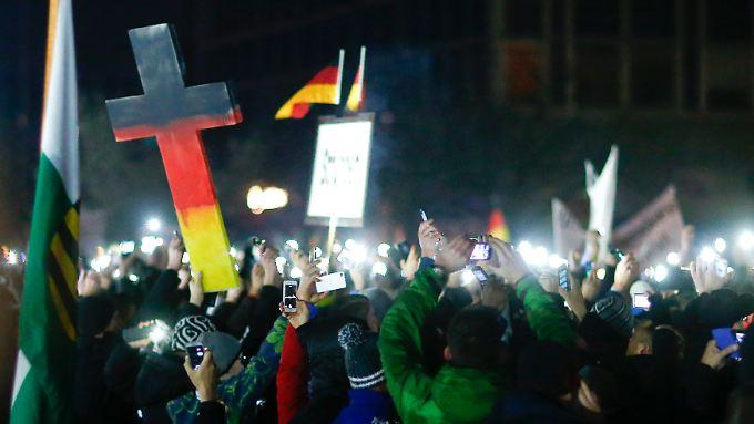 """Ein Kreuz in Schwarz-Rot-Gold auf einer Pegida-Demo in Dresden: """"Unvereinbar mit dem christlichen Glauben."""""""