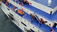 """An Deck der """"Norman Atlantic"""" warten die Menschen auf Rettung aus der Luft. Aus Sicherheitsgründen haben sie orangefarbene Schwimmwesten angelegt."""