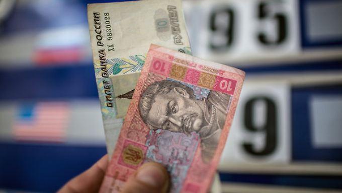 Keine Gewinner: Im Zuge der Krise verloren sowohl der russische Rubel (l.), als auch die ukrainische Hrywnja an Wert.