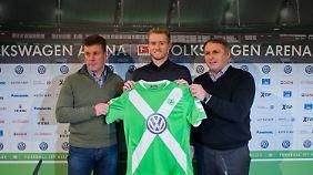Neuzugang André Schürrle steht bei seiner Vorstellung beim Fußball-Bundesligisten VfL Wolfsburg mit Trainer Dieter Hecking (l) und Manager Klaus Allofs in der Volkswagen Arena in Wolfsburg.