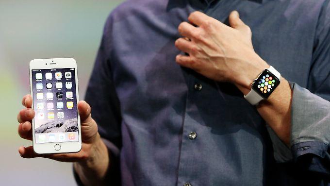 Und so soll sie aussehen: Im vergangenen September führte Appple-Chef Tim Cook (nicht ganz im Bild) die neue Smartwatch (r.) zusammen mit dem iPhone 6 Plus (l.) vor.