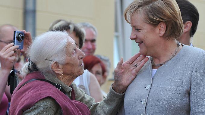 Auf dem richtigen Weg? Merkel wird von einer Bewohnerin in Diedersdorf begrüßt.