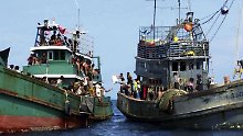 Fischer versorgen vor Thailand ein Flüchtlingsboot mit Wasser.
