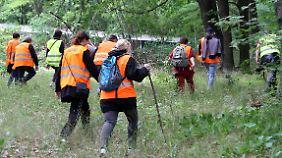 Freiwillige Helfer durchkämmen ein angrenzendes Waldgebiet.