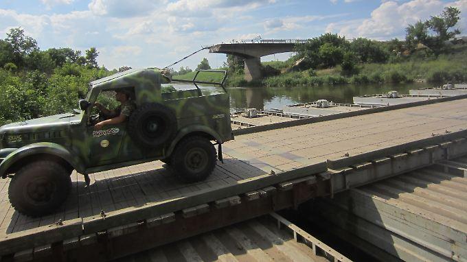 Ein Militärfahrzeug fährt am 2. Juli an einer gesprengten Brücke vorbei am Fluss Kasenny Torez in der Stadt Slowjansk im Osten der Ukraine.